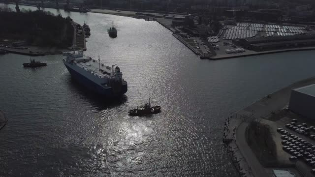 Aerial of Tugboat Towing Ship Entering Harbor Docks