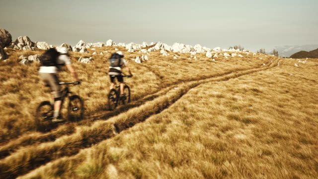 Aerial of two mountain bikers passing by the ridge video