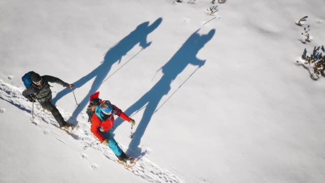 Aerial of winter mountaineers snowshoeing across valley on sunny day video