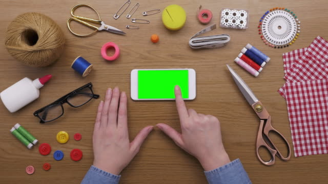 Aerial Of Woman Using Smart Phone Surrounded By Sewing Item video