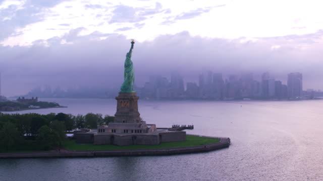 Aerial orbit of Statue of Liberty at sunrise.