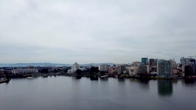 Aerial over Lake Merritt Oakland Aerial view flying over Lake Merritt with downtown Oakland in view. Skyscrapers and landmarks dot the horizon. oakland stock videos & royalty-free footage