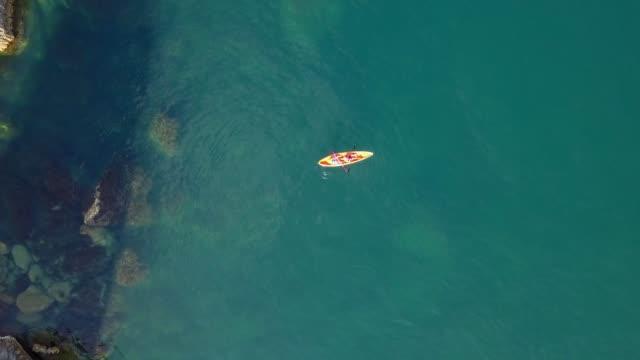 stockvideo's en b-roll-footage met luchtfoto overhead 4k schot van twee mannen in kajak-kano in de zee in de buurt van de kust van de rots - paddle