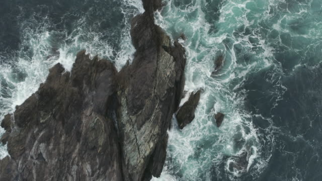 aerial overhead footage of sea waves crashing on rocky shore - cliffs stock videos & royalty-free footage