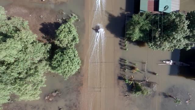 vidéos et rushes de surcharge aérienne de motos à cheval sur une rue inondée à travers un village rural - desastre natural