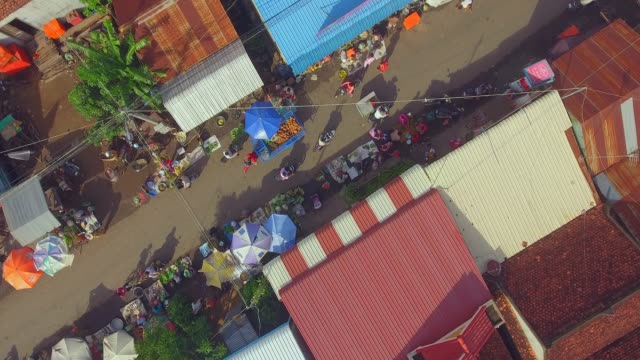aerial overhead of street scene at morning market in a small village. - cambogia video stock e b–roll