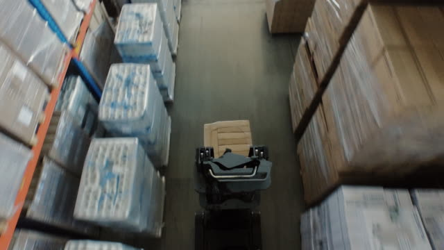 aerial overhead shot of working forklift loader inside logistic warehouse - deposito per la distribuzione video stock e b–roll