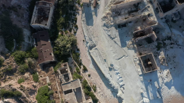 Aerial Overhead Top Down Birds Eye View of an Abandoned Factory Village at Beach on Greek Island