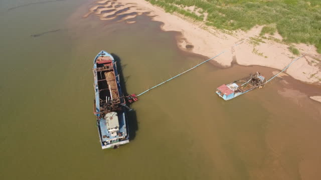 vídeos y material grabado en eventos de stock de antena panorámica captura de una operación de bombeo de arena de dragado barcos a través de un tubo de plástico - anclado