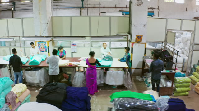 Aerial panning video of Indian group of people working factory in the packaging area