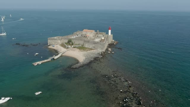 Aerial panorama of an old sea fort with a lighthouse on the small island - video
