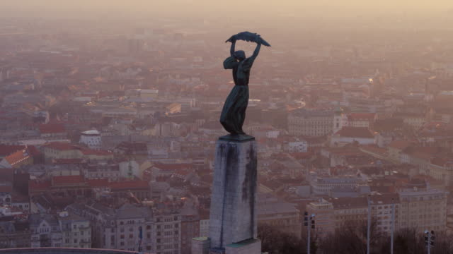 Aerial panorama of Budapest in sunrise Aerial view of the city and the Freedom Statue on the Citadella overlooking Budapest in sunrise hungary stock videos & royalty-free footage
