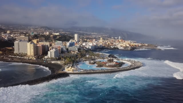 Aerial panorama of Puerto de la Cruz resorts and pools surrounded by sea waves, Tenerife, Canary islands, Spain.