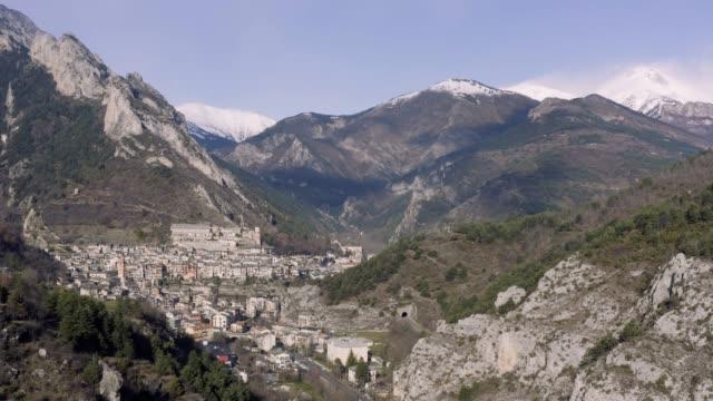vídeos de stock, filmes e b-roll de vista panorâmica aérea de uma estrada panorâmica pela bela paisagem da cidade em um vale, ponte e viaduto, o rio da montanha ao longo da estrada, montanhas cobertas de neve em um fundo - multicóptero