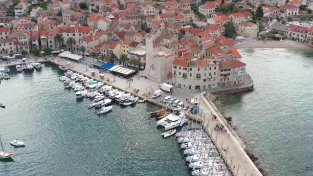 Aerial panoramic view of city Komiza - the one of numerous port towns in Croatia, is a lot of moored sailboats of a regatta, orange roofs of houses, a cathedral St.Nicholas, beach Gusarica