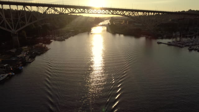 Aerial Passing Over Boats in Canal with Sun Rays Shining in Big City Bridge Rafters video