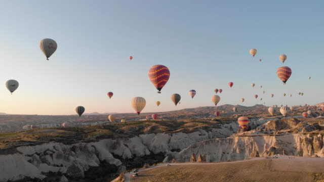 Aerial perspective flying through iconic ancient valley at sunrise Drone perspective flying past monoliths in Cappadocia, hot air balloons taking off nearby hot air balloon stock videos & royalty-free footage
