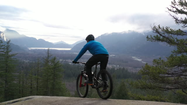 vídeos de stock e filmes b-roll de aerial perspective of mountain biker riding out on to large rock slab - man admires forest