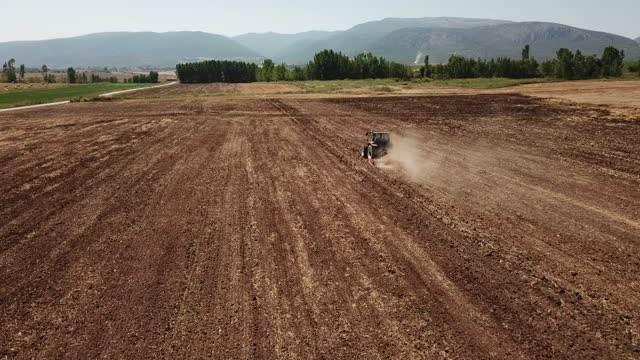 Aerial photography of a tractor that sows plowed soil using a trailer seeder in a farmer's field Aerial photography of a tractor that sows plowed soil using a trailer seeder in a farmer's field harrow agricultural equipment stock videos & royalty-free footage