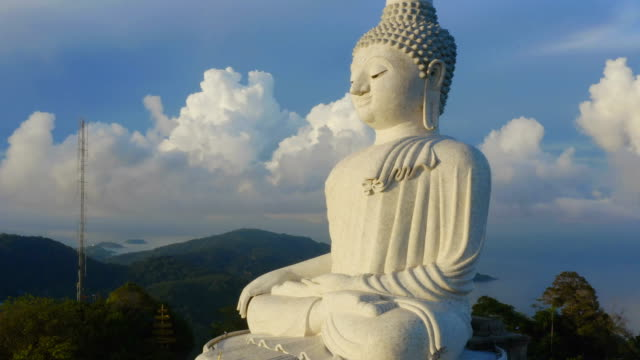 aerial photography white great Phuket big Buddha in blue sky. Phuket Big Buddha is one of the island most important and revered landmarks on the island. big Buddha is on the top of high mountain can see around the Phuket island when you are there statue stock videos & royalty-free footage