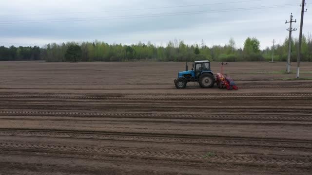 aerial: pflanzung mais gezogen pflanzer auf dem feld. tactor mit einem säen getreide auf dem feld. ein landwirt auf einem traktor mit einer saat bearbeitet das feld. - aerial view soil germany stock-videos und b-roll-filmmaterial