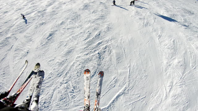 Aerial pov of people during ride on ski lift in the mountains to skiers and snowboarder on slope