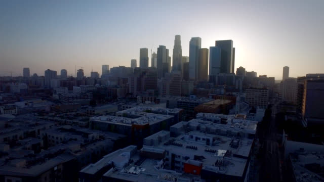Aerial pull of downtown Los Angeles California backlit with the beautiful sunset video