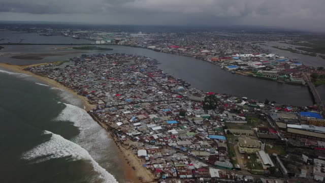 aerial pulling away from massive slum on beach - liberia video stock e b–roll