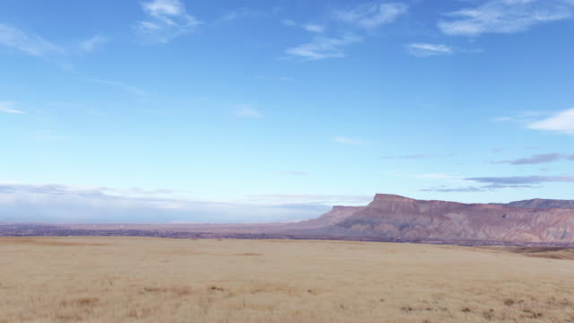 aerial pushing out drone shot of mount garfield and the bookcliffs (rocky mountains) im grand valley von western colorado mit sturmwolken am horizont - hochplateau stock-videos und b-roll-filmmaterial
