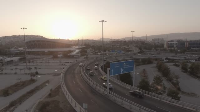 Aerial - raw footage - Athens - Piraeus - Pireas, Greece, flying above a traffic hub, bridges, tram, cable car and cars at sunset video