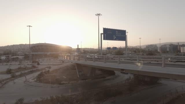 vídeos de stock, filmes e b-roll de antena - material bruto - atenas - pireus - pireu, grécia, voando acima de um concentrador de tráfego, pontes, eléctrico, teleférico e carros ao pôr do sol - ática ática