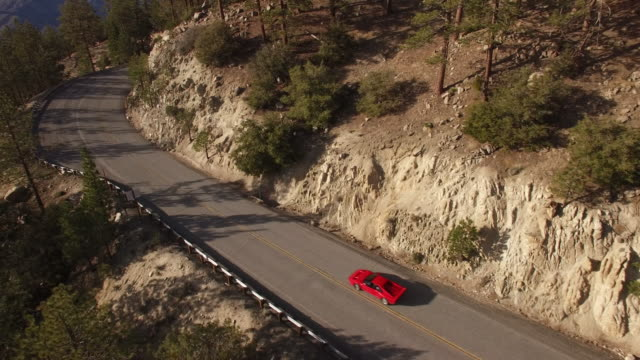 aerial red sports car chase through forest - grandangolo tecnica fotografica video stock e b–roll