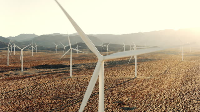 aerial reveal of windmill in wind farm in desert at sunset - turbina a vento video stock e b–roll