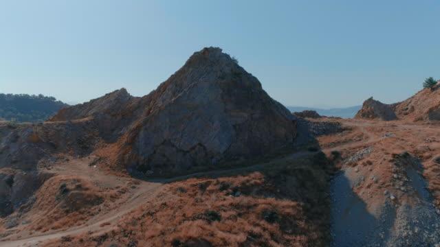 Aerial - Revealing a city through a rocky mountain video