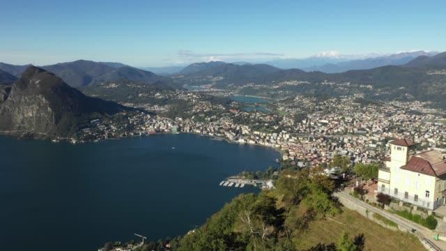 aerial revealing shot of city by a lake with mountains - szwajcaria filmów i materiałów b-roll