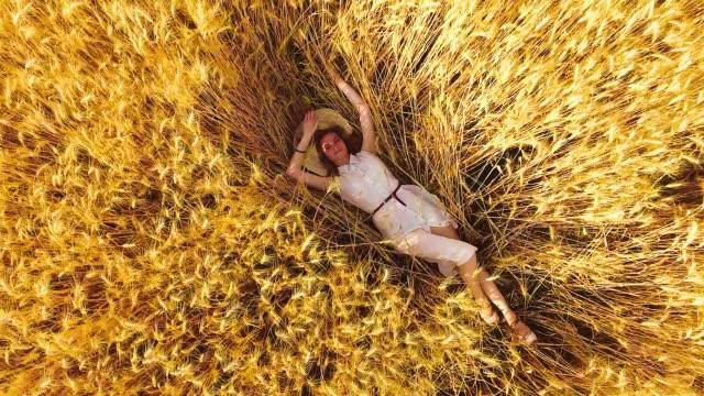 aerial rising shot young woman lying among ripe wheat ears in golden wheat field - leżeć filmów i materiałów b-roll