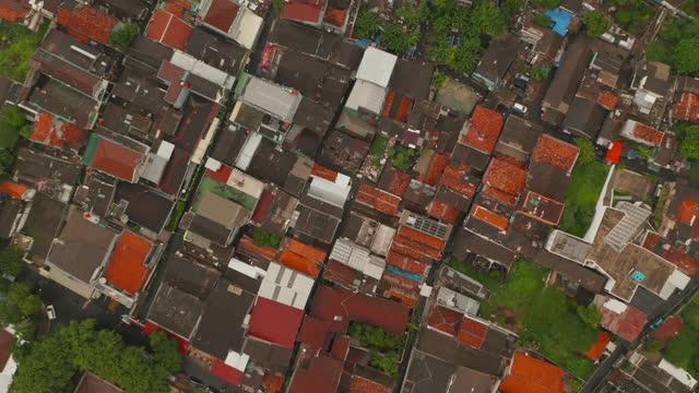 stockvideo's en b-roll-footage met lucht roterende vogels eye overhead top down view van heldere rode en oranje daken van huizen in dichte stedelijke stadswijk in jakarta - bovenkleding