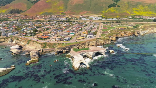 Aerial scenic remote panoramic view of the grottos on the cliff in front Pismo Beach, the small city on the Pacific Ocean, Californian West Coast, in the sunny spring day.  Aerial drone 4K UHD video with the complex backward and tilting up camera motion.