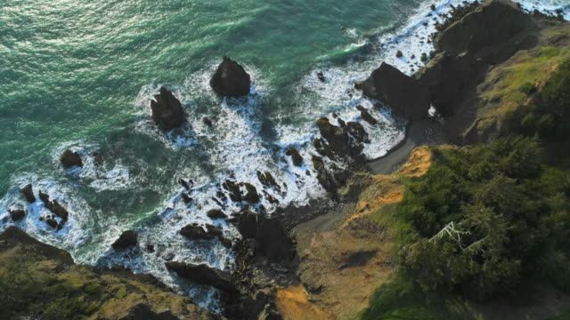 Aerial scenic view of the rocky Oregon coast nearby Brookings, USA West coast. Looking down, directly-above drone video with the panoramic camera motion.