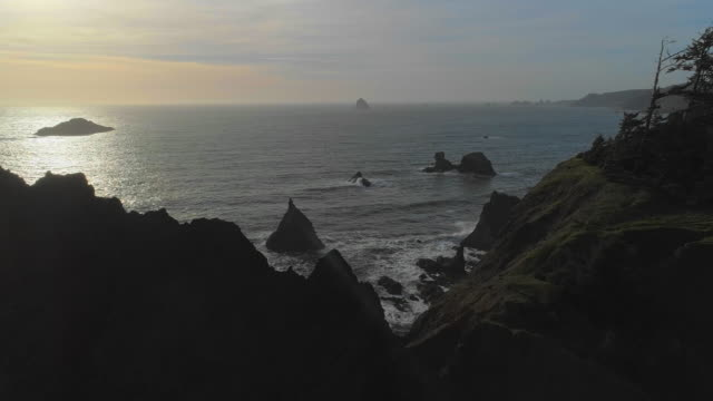 Aerial scenic view of the rocky Oregon coast nearby Brookings, USA West coast. Drone video with the panoramic and forward camera motion from the bay over rocks camera motion.