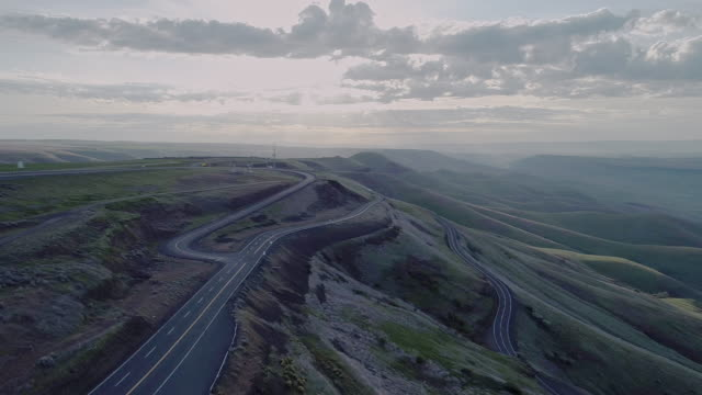 Aerial scenic view to Highway 95 nearby Lewiston, Idaho, nearby the border with Washington State. Early sunny morning at springtime. Drone video footage with the complex backward, panoramic-rotation camera motion. - vídeo