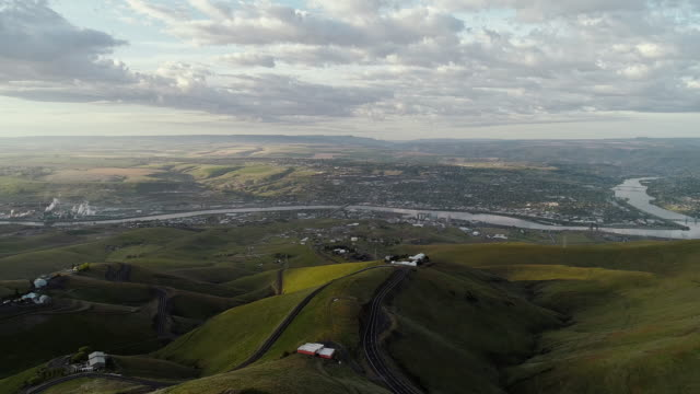 Aerial scenic view to the hills and the historic Old Spiral Highway toward two neighbor towns, Lewiston, Idaho, and Clarkston, Washington, at the states' border. Early sunny morning at springtime. Drone video footage with the forward camera motion.