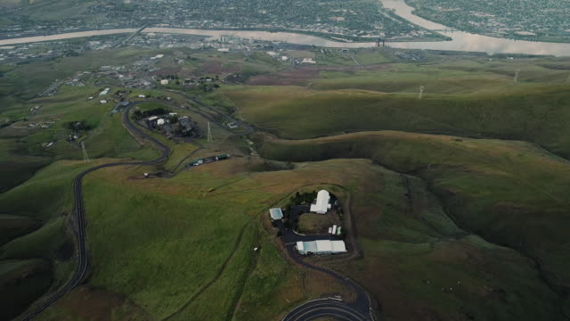 Video Aerial scenic view to the hills and the historic Old Spiral Highway toward two neighbor towns, Lewiston, Idaho, and Clarkston, Washington, at the states' border. Early sunny morning at springtime. Drone video footage with the tilting-up camera motion from