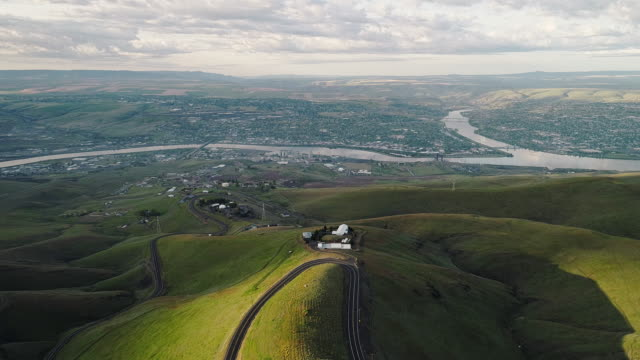 Aerial scenic view to the hills and the historic Old Spiral Highway toward two neighbor towns, Lewiston, Idaho, and Clarkston, Washington, at the states' border. Early sunny morning at springtime. Drone video footage with the backward camera motion. - vídeo
