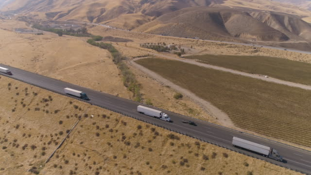 Aerial semi truck driving on the road High angle tracking shot of a semi truck on the 5 freeway in California. semi truck stock videos & royalty-free footage