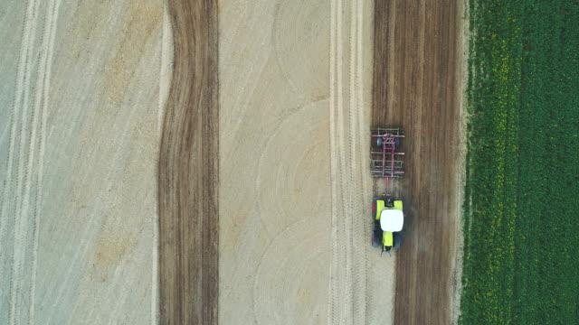 vidéos et rushes de pousse aérienne de tracteur travaillant sur le terrain. - seigle grain