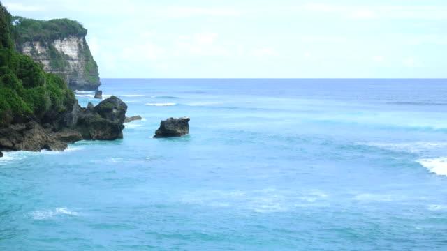Aéreo, tiro de voar a aeronave de uma bela paisagem da natureza selvagem de Bali, mar azul, rock de penhasco. 4K - vídeo