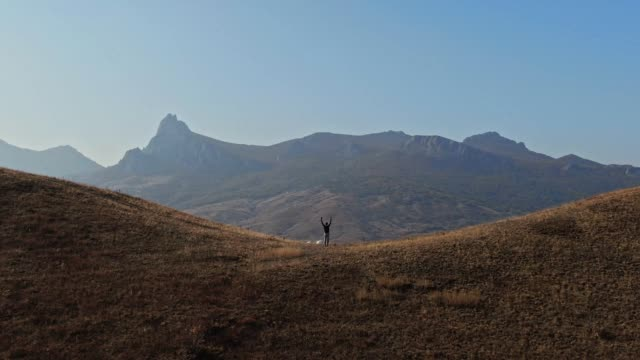 aerial shooting man doing exercise in nature against the backdrop of mountains - fisiologia video stock e b–roll