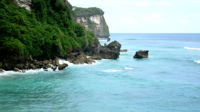 Tiro aéreo de uma bela paisagem da natureza selvagem de Bali, mar azul, rock de penhasco. 4K - vídeo