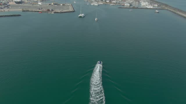 Aerial shooting of a speedboat reaching a marina bay in the Mediterranean Sea